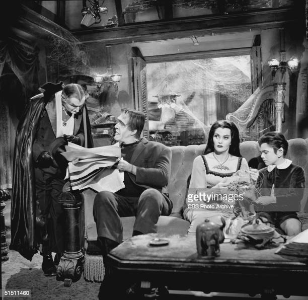 American actor and children's book author Fred Gwynne holds a newspaper and talks to Al Lewis while Canadian actor Yvonne de Carlo and child actor...