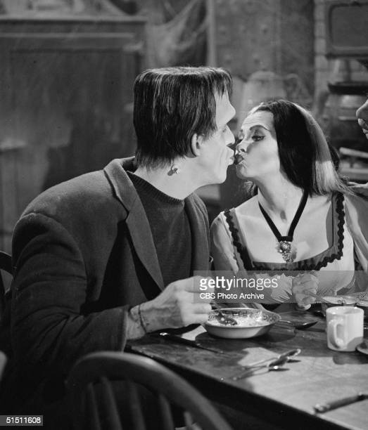 American actor and children's book author Fred Gwynne kisses Canadian actress Yvonne de Carlo at the breakfast table in a still from the CBS...