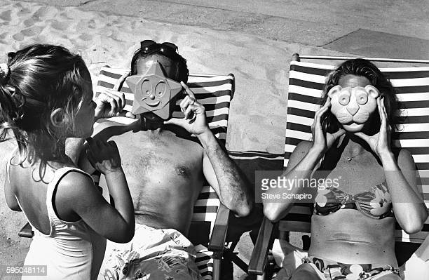 American actor and comedian Chevy Chase and his wife Jayni Chase lie in deck chairs and hold sand toys over their faces as one of their daughter...
