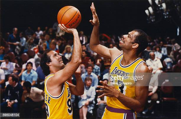 American actor and comedian Chevy Chase plays basketball with professional athlete Kareem AbdulJabbar in a scene from the film 'Fletch' 1985