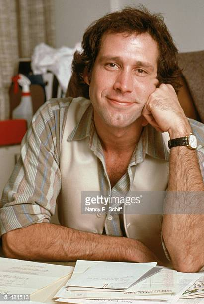 American actor and comedian Chevy Chase rests his head on his fist while seated at a desk covered with paperwork 1979