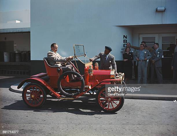 American actor and comedian Eddie 'Rochester' Anderson stands by an antique Maxwell car as fellow comedian Jack Benny sits in the driver's seat...