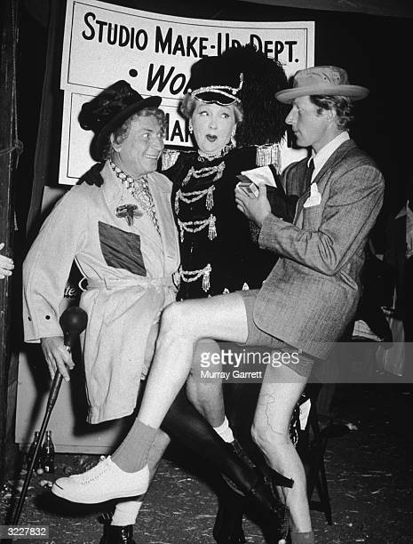American actor and comedian Harpo Marx gossip columnist Hedda Hopper and actor Danny Kaye intertwine their legs as they stand in the makeup area at a...