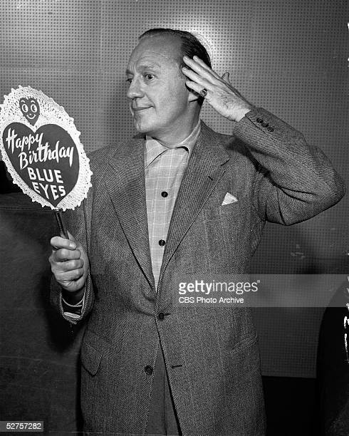 American actor and comedian Jack Benny looks into a handmirrorshaped birthday card which reads 'Happy Birthday Blue Eyes' and pantomimes vain...