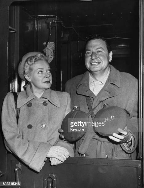 American actor and comedian Phil Harris and his wife actress Alice Faye arrive at Grand Central Station in New York armed with bottles of water in...
