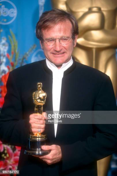 American actor and comedian Robin Williams , dressed in a long suit coat, poses with his Academy Award for Best Actor in a Supporting Role for his...