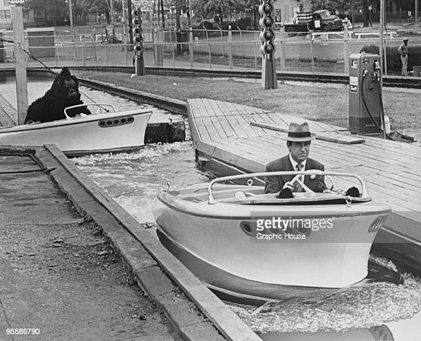 American actor and comedian Soupy Sales is pursued by a man a gorilla suit whilst driving a speedboat circa 1965