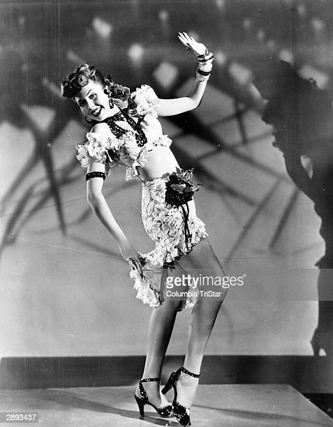 American actor and dancer Ann Miller performs a tap dance routine in a half length shirt and ruffled skirt in a scene from the film 'The Thrill of...