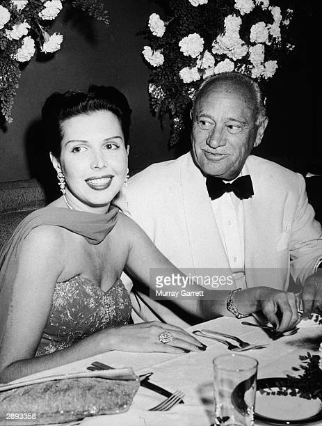 American actor and dancer Ann Miller sits at a table with American hotelier Conrad Hilton at the Mocambo Nightclub for a Damon Runyon Cancer Benefit...