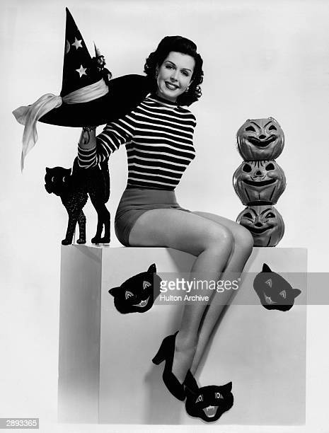 American actor and dancer Ann Miller wears a striped shirt and shorts as she sits on a box adorned with decorations of pumpkins and black cats circa...