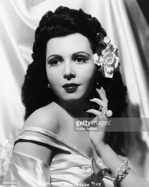 American actor and dancer Ann Miller wears an offtheshoulder gown and a flower in her hair in a studio portrait 1943