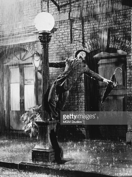 American actor and dancer Gene Kelly swings from a lamp post in a still from the film 'Singin' In The Rain' directed by Kelly and Stanley Donen 1952