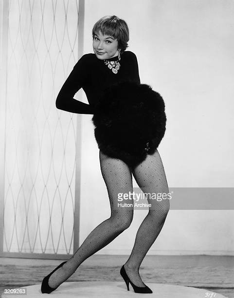 American actor and dancer Shirley MacLaine poses in a unitard fishnet stockings and high heels while holding a fur muff in a fulllength promotional...