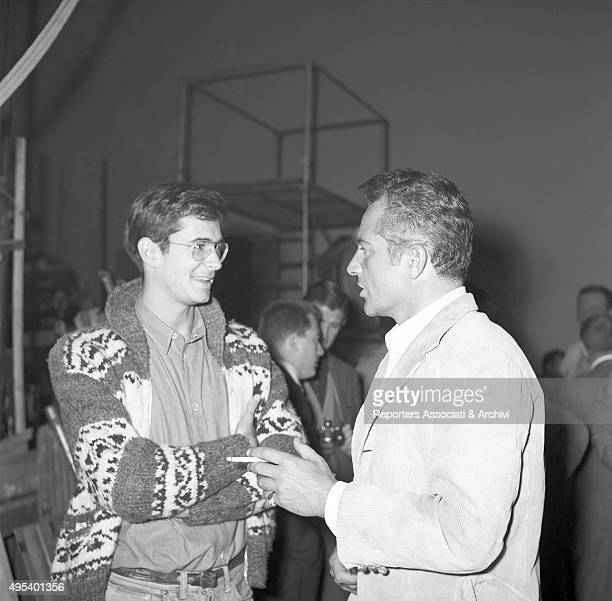 American actor and director Anthony Perkins talking to Italian actor and director Rossano Brazzi at Cinecittà studios Rossano Brazzi wears the stage...