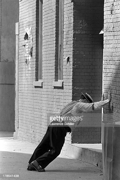 American actor and director Buster Keaton leans against a wall in preparation for a scene from an unidentified television program Culver City...