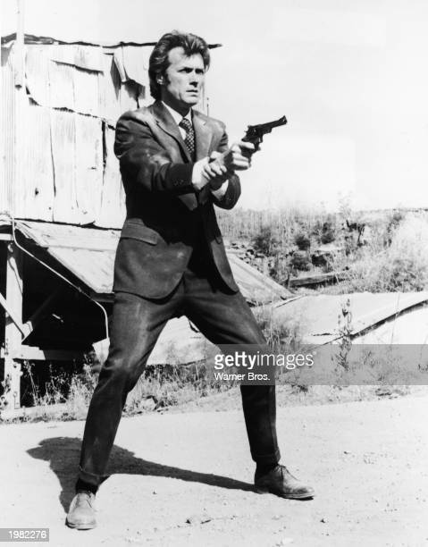 American actor and director Clint Eastwood takes a firing stance aiming a pistol in a still from the film 'Dirty Harry' directed by Don Siegel 1971