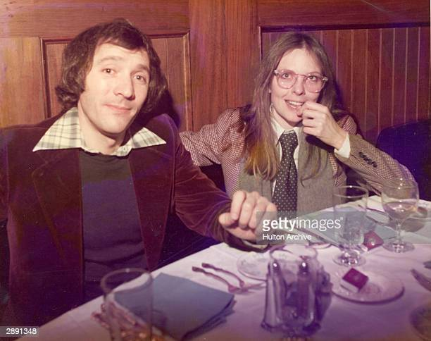 American actor and director Diane Keaton and an unidentified man sit at a table in a restaurant circa 1980 Keaton is wearing a hound's tooth jacket...