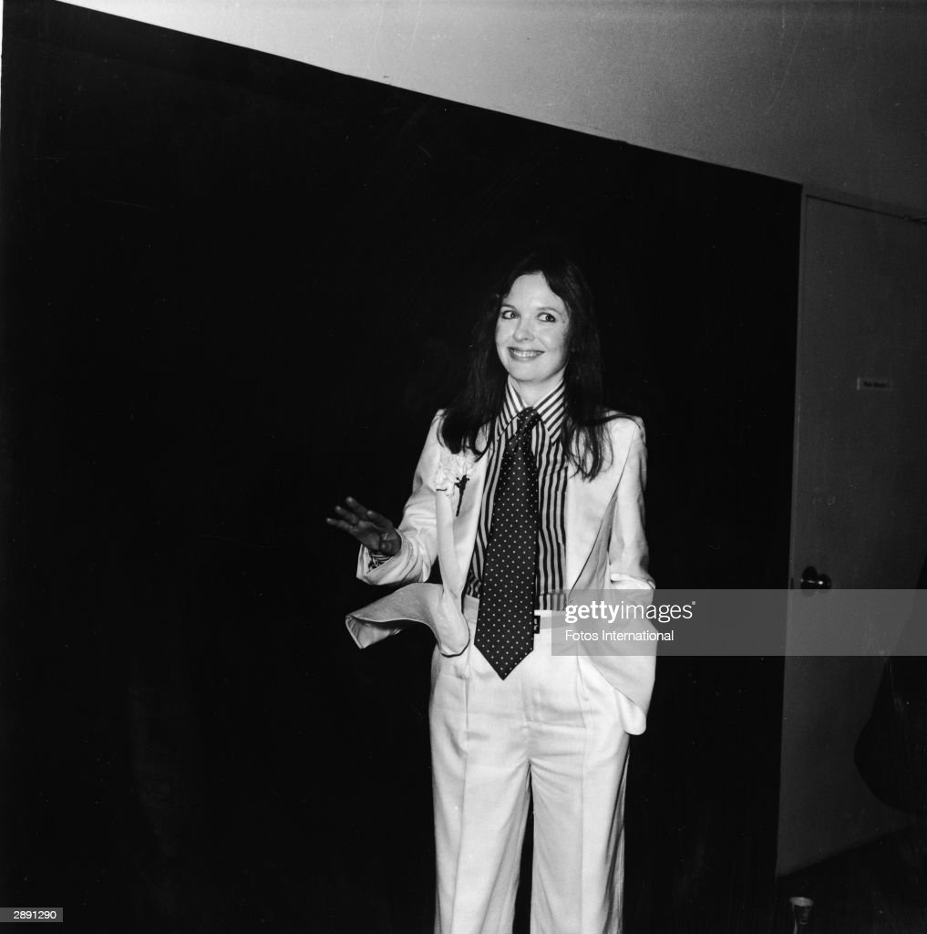 American actor and director Diane Keaton poses with a big smile and tilted head at the 48th Academy Awards and wears a white suit with a carnation in the lapel, striped shirt, and polka dot tie, Los Angeles, California, March 29, 1976.