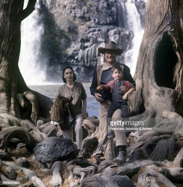 American actor and director John Wayne being photographed with his son Ethan and his wife Pilar Pallete during a break on the set of the film 'The...
