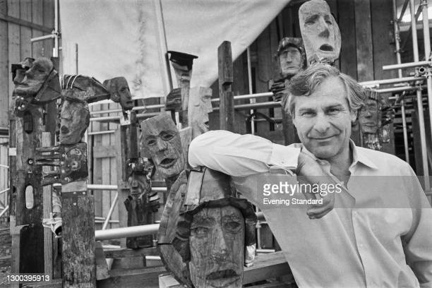 American actor and director Sam Wanamaker with an array of wooden masks, UK, 29th August 1972.