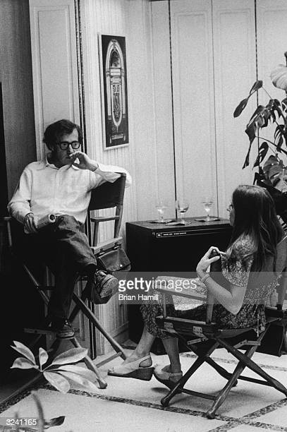 American actor and director Woody Allen sits in his director's chair and talks to actress Shelley Duvall on the set of his film, 'Annie Hall'.