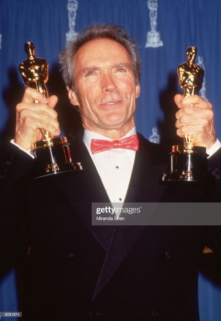 American actor and film director Clint Eastwood holds up his two Oscars for Best Director and Best Actor, for his film, 'Unforgiven,' in front of a blue curtain at the Academy Awards, Los Angeles, California.