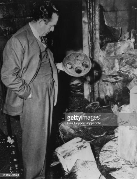 American actor and film director Harold Lloyd holds a film reel as he surveys the remains of his collection of films following an explosion and fire...