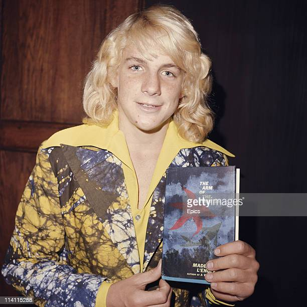 American actor and filmmaker Darby Hinton in a brightly coloured shirt poses with a copy of 'The Arm Of The Starfish' by Madeleine L'Engle United...