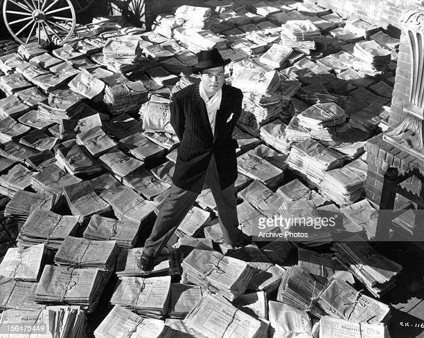 American actor and filmmaker Orson Welles standing on stacks of newspapers in a scene from the film 'Citizen Kane', 1941.