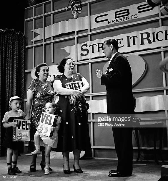 American actor and game show host Warren Hull speaks to two female contestants who stand with two small children and hold boxes of Vel washing...