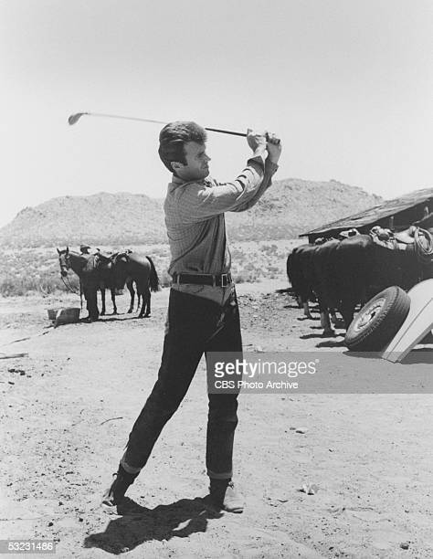 American actor and later director Clint Eastwood wears chaps while he practices his golf swing as a horse looks on during a break in the shooting of...