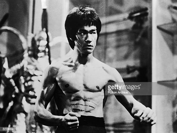 American actor and martial artist Bruce Lee poses in a fighting stance with his arms by his waist in a still from the film 'Enter The Dragon' He has...