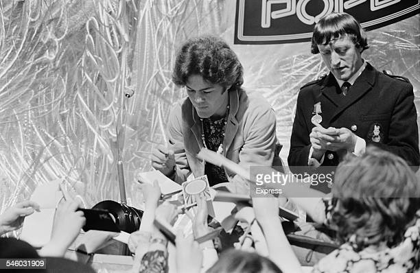 American actor and musician Micky Dolenz with English DJ and television presenter Jimmy Savile signing autograph books for fans on the set of the...