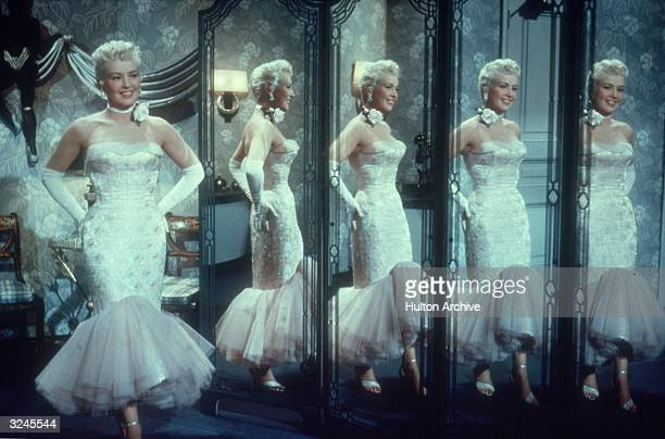 American actor and pinup Betty Grable wearing a white gown reflected in the multiple mirrors of a powder room in a still from director Jean...