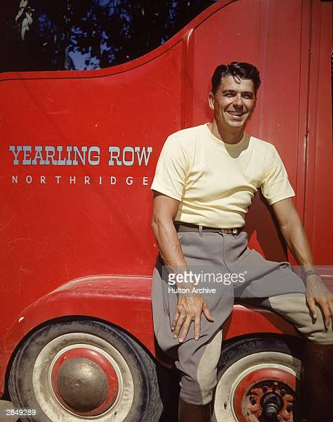 American actor and politician Ronald Reagan poses in front of a red trailer belonging to the Yearling Row ranch, Northridge, California, circa 1960....