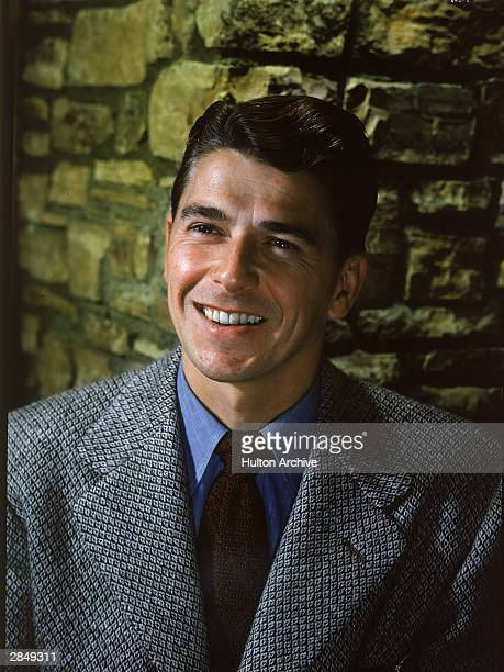 American actor and politician Ronald Reagan poses in front of rough brick wall for a portrait circa 1960s