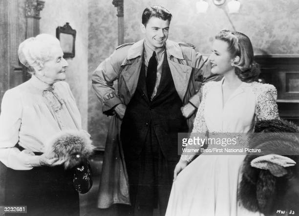 American actor and politician Ronald Reagan smiles at actor Priscilla Lane as actor May Robson looks on in a still from director Curtis Bernhardt's...