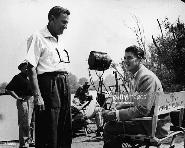 American actor and politician Ronald Reagan talks with an unidentified crew member on the set during the filming of an episode of 'General Electric...