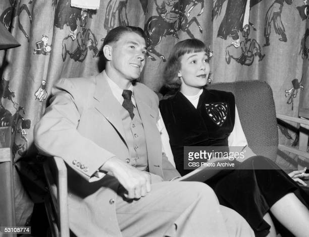 American actor and President Ronald Reagan and his wife, American actress Jane Wyman sit on a couch in a green room and relax prior to performing on...