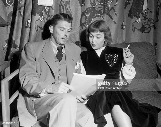 American actor and President Ronald Reagan and his wife American actress Jane Wyman sit on a couch in a green room and read their lines from a script...