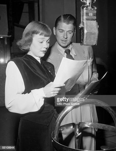 American actor and President Ronald Reagan and his wife American actress Jane Wyman read from scripts and speak into a hanging microphone in a radio...