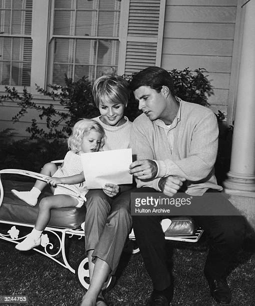 American actor and rock n' roll singer Rick Nelson sits outdoors on a lawn chair with his wife Kristin Harmon and their daughter Tracy