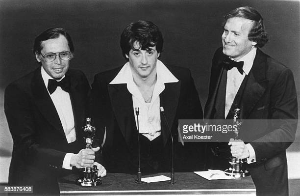 American actor and screenwriter Sylvester Stallone with producers Irwin Winkler and Robert Chartoff receive the Best Picture award for their movie...