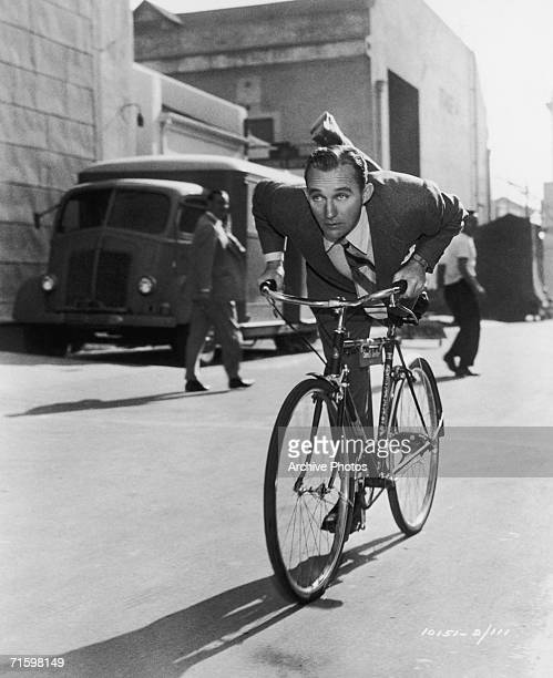 American actor and singer Bing Crosby demonstrates some fancy footwork whilst crossing the Paramount studio lot on his way to work on whimsical Irish...
