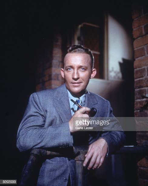 American actor and singer Bing Crosby poses for a portrait holding a pipe in his hand