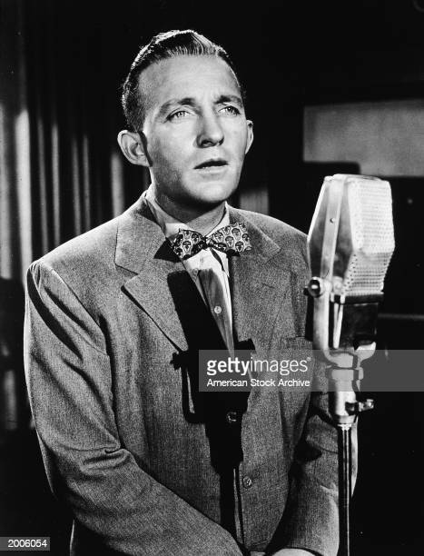 American actor and singer Bing Crosby sings into a microphone circa 1945