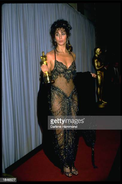 American actor and singer Cher holds her Academy Award for Best Actress for her role in director Norman Jewison's film 'Moonstruck' Shrine Civic...