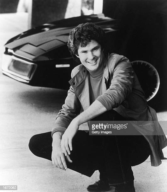 American actor and singer David Hasselhoff poses next to the computerized car KITT in a promotional portrait for the television series 'Knight Rider'...