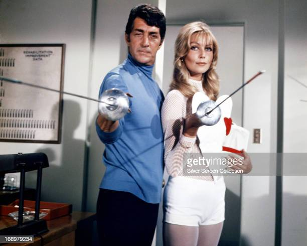 American actor and singer Dean Martin as Matt Helm and Austrian actress Senta Berger as Francesca Madeiros holding fencing foils in a publicity still...