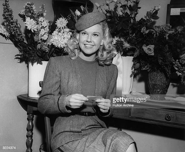 American actor and singer Doris Day smiling as she sits in front of bouquets of flowers in her dressing room on the set of director Michael Curtiz's...